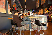 A young person uses his multimedia device in a trendy coffee shop in the hip neighborhood of Wicker Park in Chicago, IL, USA.