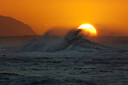 Setting sun silhouettes the surf on Oahu's north shore, Hawaii