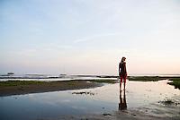 Woman walks along tidal mudflats of Wadden sea at low tide, Island of Juist, Germany