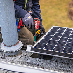A Revision Energy employee installing solar panels on a single family home in Lowell, Massachuetts.