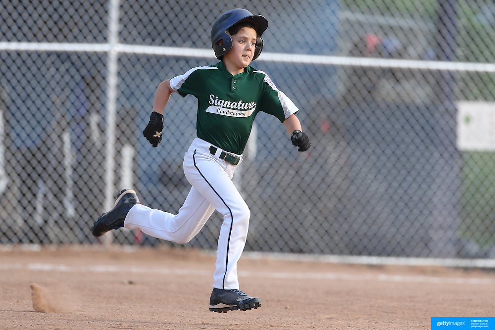 A batter runs to second during the Norwalk Little League baseball competition at Broad River Fields,  Norwalk, Connecticut. USA. Photo Tim Clayton