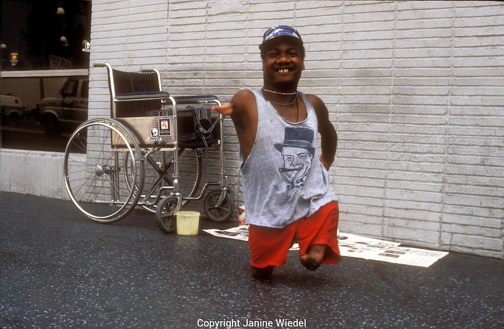 Man with amputated limbs dancing in the street.