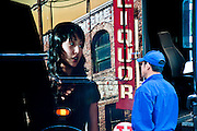 A bus driver stares at the picture of an Asian girl pasted up on a bus, Manhattan, New York, 2009.