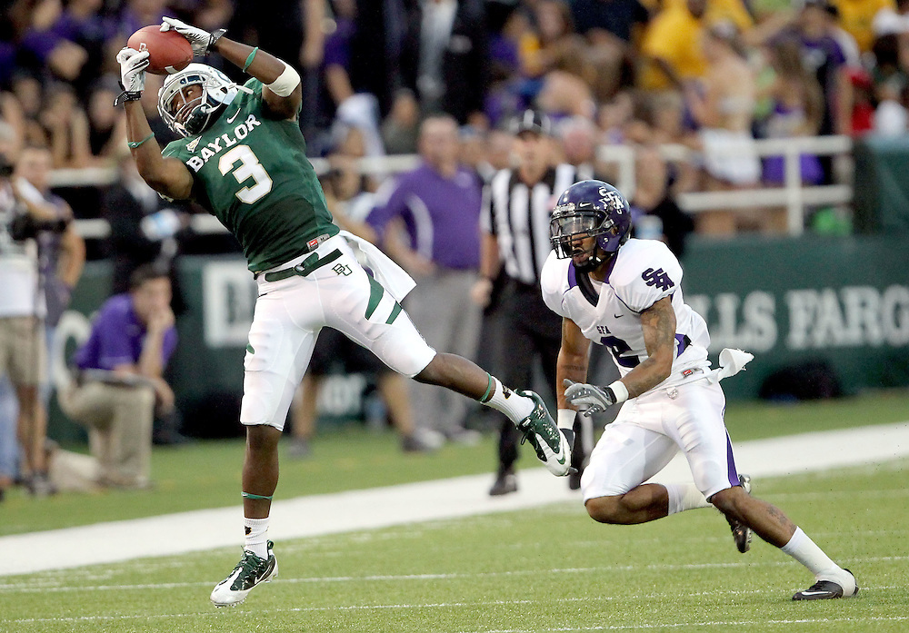 Baylor wide receiver Lanear Sampson (3) catches a pass for yards as Stephen F. Austin defensive back Ben Wells (2) defends during an NCAA college football game, Saturday, Sept. 17, 2011, in Waco, Texas. Baylor won 48-0.