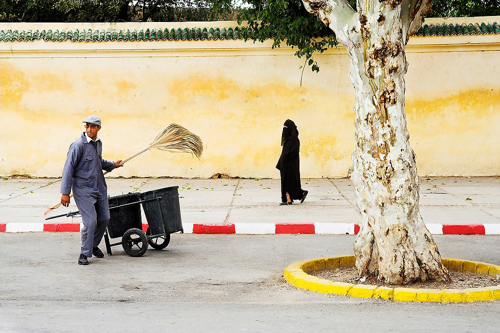 A veiled Muslim woman walks by a garbage collector holding up a broom along a well maintained sidewalk in Fes El-Jdid, Morocco.