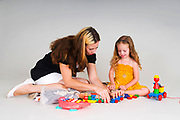 Mother and daughter of 3 play with building blocks
