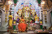The officiating priest worships the Kumari in front of Devi Durga. In front of Adu, the girl who is manifestation of Kumari, is a plate with naivedya (special offering of food to the gods, which are uncooked, consisting mostly of fruits, sweets, cereal, sugar and uncooked rice). Devi Durga and her associated gods and goddesses are seen as living entities with 'prana' (life), hence they are offered food just like humans. This is later distributed as prasada to devotees.