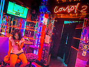 """22 MAY 2014 - BANGKOK, THAILAND: A woman in the Cowboy 2, a bar in the Soi Cowboy """"adult entertainment"""" district, checks her smart phone while the TV above her broadcasts the Thai army announcement of a coup replacing the civilian government. The Thai army suspended civilian rule, suspended the constitution and declared the """"military takeover of the nation."""" The announcement came just before evening as a meeting between civilian politicians and the army was breaking up with no progress towards resolving the country's political impasse. Civilian politicians were arrested when the meeting ended. The army also declared a curfew from 10PM until 5AM.    PHOTO BY JACK KURTZ"""