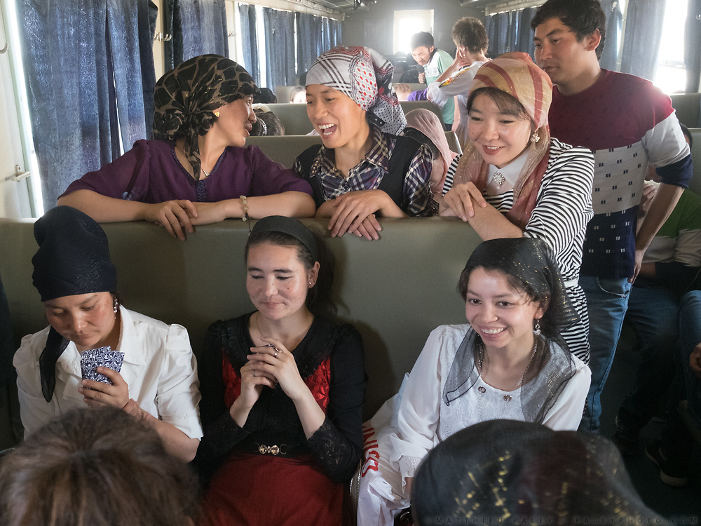 Students from the Hotan university go for a visit to Kashgar for exams. They play card in the train. Life inside the train - mostly Muslim Uighur people  ride this train.
