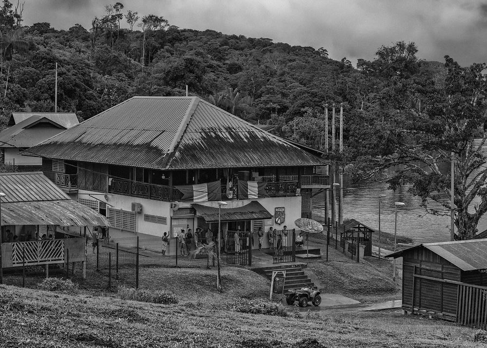 Camopi, Guyane, 2015.<br /> <br /> Centre névralgique de la commune de Camopi, ce bâtiment administratif abrite à la fois la mairie, le bureau de poste, les services d'aide sociale et un « Point d'Information Jeunesse » qui rempli le rôle d'agence pour l'emploi. La mairie est le plus souvent fermée, en l'absence du maire en réunion à Cayenne. La poste est ouverte du lundi au vendredi de 8h00 à 10h30,  le « Point d'Information Jeunesse » accueille les jeunes désoeuvrés du bourg toute la matinée, ou pas.