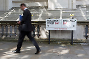 A man walks past the signpost where Whitehall SW1 becomes Parliament Street in Westminster, on 19th August 2019, in London, England.
