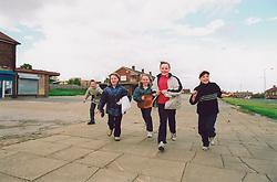 Children playing near shops Bradford council housing estate UK