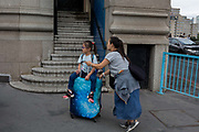 Chinese visitors to London push their baggage with two children riding on top, on 14th August 2017, on Tower Bridge, in London, England.