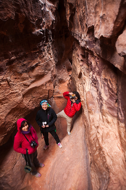 Leora Leshem (l-r), Yoesun Lim, and SeongRyeong Bak explore the Khazali slot canyon in Wadi Rum, Jordan.