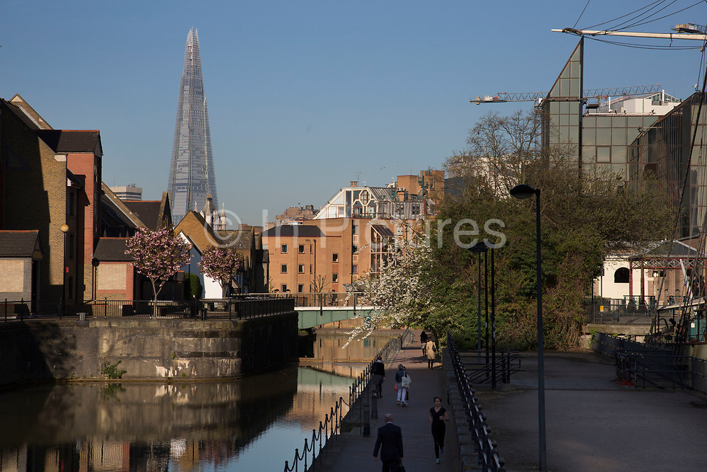 Housing along remnants of London Dock waterways in Wapping looking towards the Shard in London, UK. The London Docks were one of several sets of docks in the historic Port of London. They were constructed in Wapping downstream from the City between 1799 and 1815.