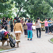A large group of local women do Tai Chi in the morning on the banks of Hoan Kiem Lake in the heart of Hanoi, Vietnam.