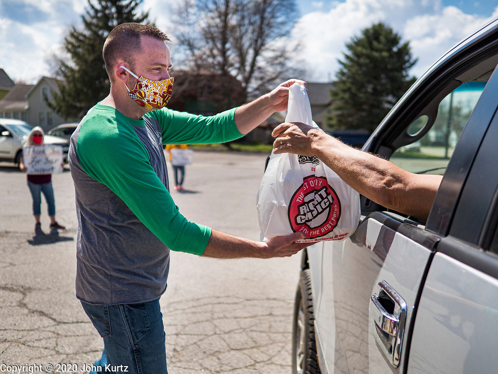 "26 APRIL 2020 - JEWELL, IOWA: GARREN ZANKER, hands a bag of ""grab and go"" roast pork dinners to a motorist in Jewell during a fund raiser Sunday. Jewell, a small community in central Iowa, became a food desert when the only grocery store in town closed in 2019. It served four communities within a 20 mile radius of Jewell. Some of the town's residents are trying to reopen the store, they are selling shares to form a co-op, and they hold regular fund raisers. Sunday, they served 550 ""grab and go"" pork roast dinners. They charged a free will donation for the dinners. Despite the state wide restriction on large gatherings because of the COVID-19 pandemic, the event drew hundreds of people, who stayed in their cars while volunteers wearing masks collected money and brought food out to them. Organizers say they've raised about $180,000 of their $225,000 goal and they hope to open the new grocery store before summer.            PHOTO BY JACK KURTZ"