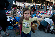 Hungary, Budapest, Keleti Station. A young refugee girl tries on a donated coat over her t shirt which says 'Swanky'.