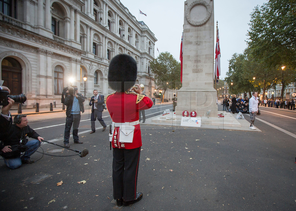 © Licensed to London News Pictures. 23/10/2014.  London.  The Royal British Legion launched the 2014 Poppy Appeal at sunrise this morning at the Cenotaph memorial.  A bugler from the British Army launches a series of 30 minute vigils to commemorate fallen soldiers of WW1.  The Poppy Appeal is The Royal British Legion's largest annual charity campaign. In a little over two weeks, some 45 million poppies will be distributed by 350,000 dedicated collectors with the aim of raising £40 million.        Photo credit : Alison Baskerville/LNP