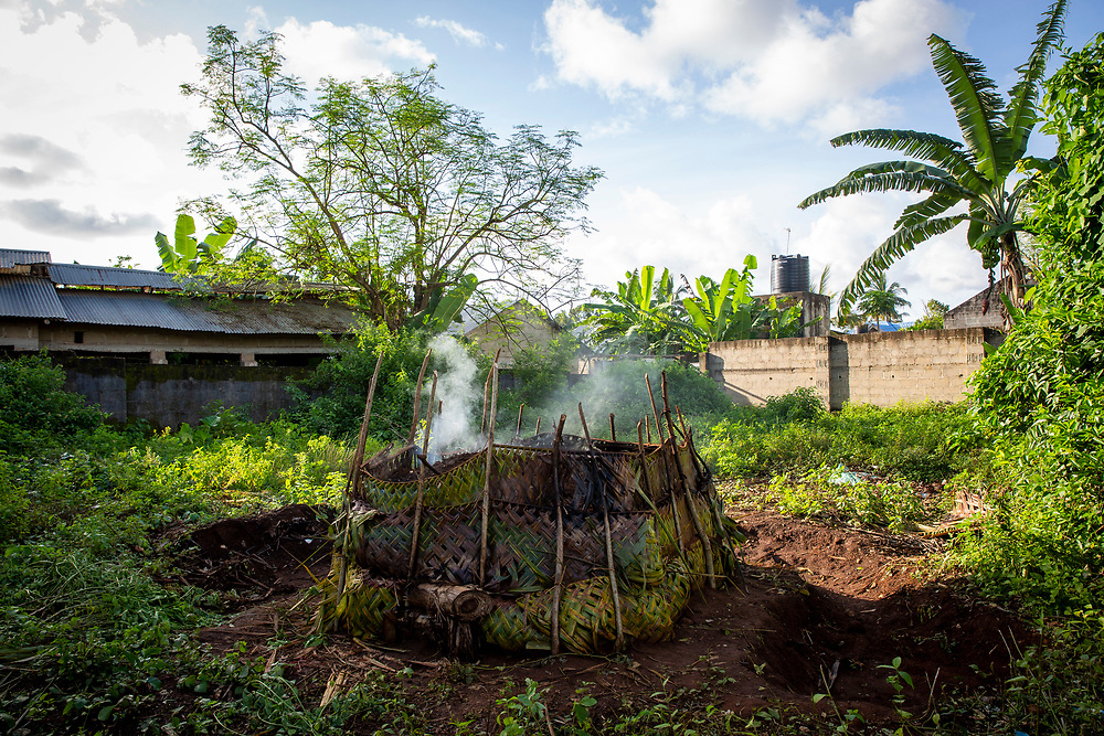 A home made charcoal making system in Stone Town, Zanzibar. When a tree is felled to make charcoal it is chopped up and set light to then buried under soil and palm leaves and left to smoulder for several days. The wood burns at high temperatures which pyrolyzes the wood. The making and use of charcoal contributes to deforestation and air pollution. It is an affordable fuel used for cooking across Africa.  (photo by Andrew Aitchison / In pictures via Getty Images)