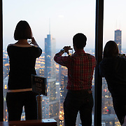 Tourists snap photos of the downtown Chicago skyline as seen from the 96th floor of the John Hancock Center on Monday, Oct. 6, 2014 in Chicago, Illinois. (AP Photo/Alex Menendez)