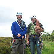 Portrait of 2 male climbers wearing safety equipment and carrying ropes at Sutton Bank, North York Moors, North Yorkshire, UK