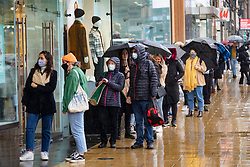 Edinburgh, Scotland, UK. 3 October, 2020. An amber rainfall warning for the east of Scotland did not deter many shoppers from walking along Princes Street in Edinburgh today. Persistent heavy rain fell throughout the morning and afternoon. Pictured; People queuing outside H&M shop. Iain Masterton/Alamy Live News