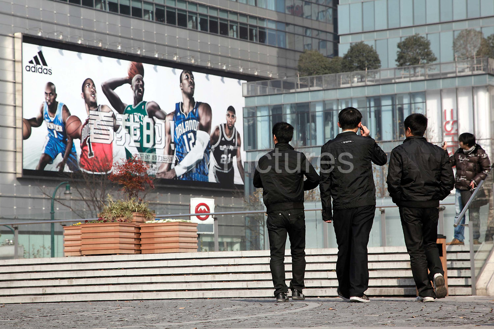 Pedestrians walk near a large Adidas advertisement featuring NBA stars in Shanghai, China on 29 December, 2009.  The National Basketball Association has enjoyed enormous popularity amongst the youth of the country.