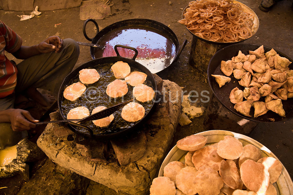 A cook prepares Samosas and Jalebi ( spirals of sweet batter) at the annual Sonepur animal fair, Bihar, India.