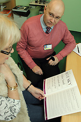 Patient looking at Harsant vision chart in consulting room in eye clinic at QMC hospital, Nottingham.
