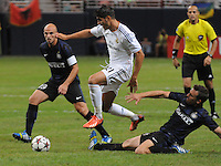 Football - Real Madrid defeated Inter Milan 3-0 in an international friendly game played on Saturday August 10, 2013 at the Edward Jones Dome in St. Louis, Missouri, USA.  The game was played on a real grass field, that was brought in as huge rolls of sod and rolled out inside the stadium, which normally is the home of the St. Louis Rams of the National Football League. Real Madrid forward Alvaro Morata (21, center) leaps over an attempted slide tackle by Internazionale midfielder Hugo Campagnaro (14, right) in the second half.  At left is Internazionale defender Fredy Guarin (13).