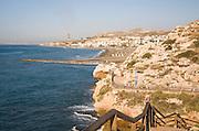 Coastline with breakwater groyne, waves and beach at La Cala del Moral, Malaga, Spain