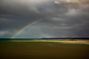 A rainbow stretches across the sky over Mont Saint-Michel Bay over the tidal island of Tombelaine in Normandy, France.