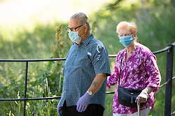©Licensed to London News Pictures 22/06/2020<br /> Greenwich, UK. An elderly couple wearing protective face masks while on their park walk. A warm sunny day in Greenwich park, Greenwich, London. The UK to enjoy hot heatwave weather this week with temperatures set to bring the hottest day of the year so far. Photo credit: Grant Falvey/LNP
