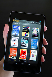 Man holding  Google Nexus tablet computer running android operating system and browsing e-books in Kindle library