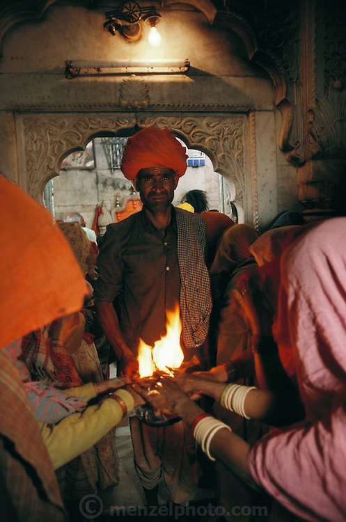 Pre-dawn worshipers with flaming camel dung at the Hindu Rat Temple in Deshnoke, Rajasthan, India. This ornate Hindu temple was constructed by Maharaja Ganga Singh in the early 1900s as a tribute to the rat goddess, Karni Mata..