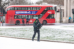 © Licensed to London News Pictures. 09/02/2021. London, UK. Commuters head to work in a snowy Hyde Park Corner, London this morning as Storm Darcy hits the South East with yet more snow and freezing temperatures today. The Met Office have issue numerous weather warnings for heavy snow and ice with disruption to travel, power cuts and possible stranded vehicles as the bad weather continues throughout the country.  Photo credit: Alex Lentati/LNP
