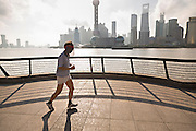 A man jogs early morning on the Bund against the skyline of modern Shanghai, China