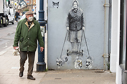 © Licensed to London News Pictures 28/04/2021. Whitstable, UK. An elderly man walking past a Catman mural of the Queen. People in Whitstable High Street in Kent wearing masks to protective themselves against the threat of Coronavirus. Photo credit:Grant Falvey/LNP
