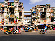 24 FEBRUARY 2015 - PHNOM PENH, CAMBODIA: A street view of the White Building. The White Building, the first modern apartment building in Phnom Penh, originally had 468 apartments, and was opened the early 1960s. The project was overseen by Vann Molyvann, the first Cambodian architect educated in France. The building was abandoned during the Khmer Rouge occupation. After the Khmer Rouge were expelled from Phnom Penh in 1979, artists and dancers moved into the White Building. Now about 2,500 people, mostly urban and working poor, live in the building. Ownership of the building is in dispute. No single entity owns the building, some units are owned by their occupants, others units are owned by companies who lease out apartments. Many of the original apartments have been subdivided since the building opened and serve as homes to two or three families. The building has not been renovated since the early 1970s and is in disrepair. Phnom Penh officials have tried to evict the tenants and demolish the building but residents refuse to move out.   PHOTO BY JACK KURTZ
