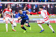 Johan Branger of Oldham Athletic (22) escapes James Coppinger of Doncaster Rovers (26) and Danny Andrew of Doncaster Rovers (3) during the The FA Cup fourth round match between Doncaster Rovers and Oldham Athletic at the Keepmoat Stadium, Doncaster, England on 26 January 2019.