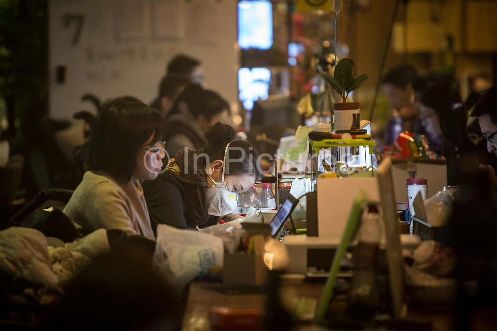 A resident wears a face mask while working at her station inside a You+ community in Beijing, China, on Monday, Nov. 30, 2015. Nearly 5,000 people across China have moved into co-living spaces called You+, a name meant to inspire young people to infinitely expand their horizons. About 60 startups call the Beijing location home — developing mobile games, services that improve sleep patterns and much more.