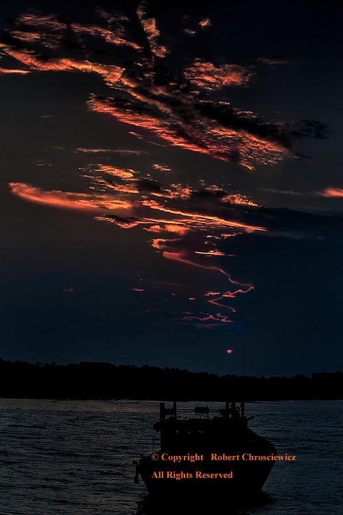 Witness in Silhouette: A lone fishing boat stands at harbour as the sky takes on a fiery disposition; when a jagged array of clouds turn as red as the sun, Hoi An Vietnam.