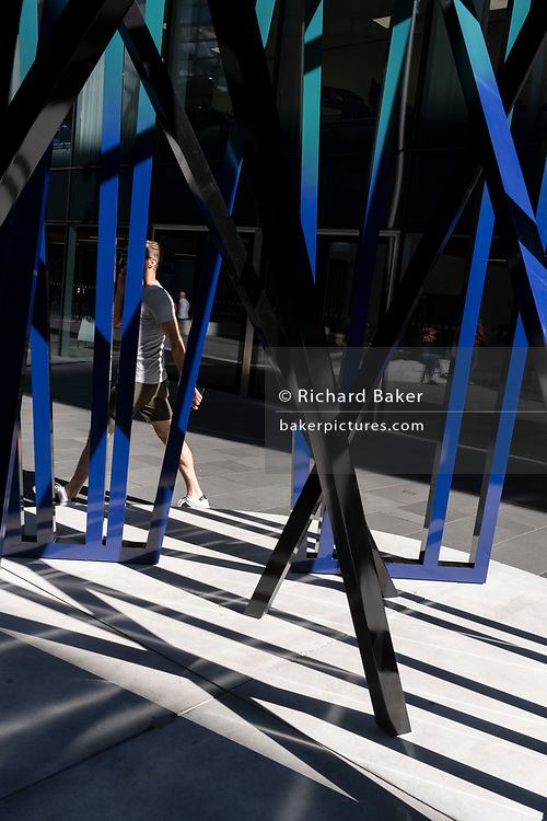 A City worker walks past the sculpture entitled 'Cosmos', an artwork by Eva Rothschild in the City of London, the capital's financial district, on 24th September 2021, in London, England. Cosmos (2019) is composed of three 3.5m high slatted structures which lean and support each other and is part of the summer's Art In The City' project.