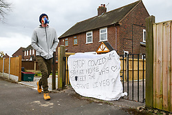 A person with a gas mask walks by a gated house with a hand drawn sign warning people to stay at home, stop the spread of COVID-19, protect the NHS, and save lives is displayed as the UK continues in lockdown to help curb the spread of the coronavirus.