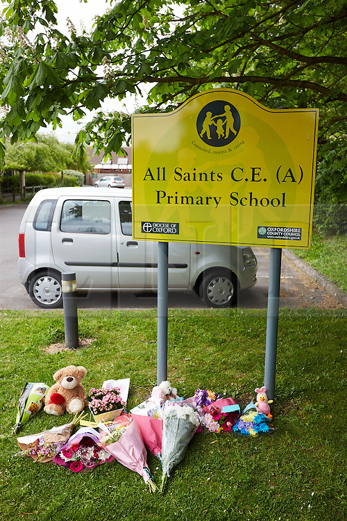 © Licensed to London News Pictures. 25/05/2015. DIDCOT, UK. Flowers and tributes left outside All Saints Primary School, where 6 year old Derrin Jordon attended. Police found three bodies, including her's, in Vicarage Road, Didcot, on Saturday evening and  continue to search for Jed Allen in connection with the deaths. Photo credit : Cliff Hide/LNP