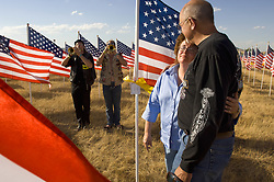 Christopher's Flag. Sturgis, SD. 2006<br /> <br /> Limited Edition Print from an edition of 50. Photo ©2006 Michael Lichter.<br /> <br /> Description: Christopher's mother and her husband Al stand beside his flag at the Buffalo Chip's Healing Field Flag Memorial as Bugles Across America twins Matt and Chas Dickson play taps. We all cry.