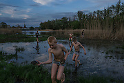 Slovyansk, Ukraine - April 23, 2014: A boy carries a couple of turtles as he and other friends fish at dusk near a check point controlled by pro-Russian demonstrators in Slovyansk, eastern Ukraine. CREDIT: Photo by Mauricio Lima for The New York Times