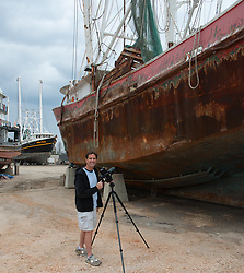 man by a large ship cleaning the hull and photographing
