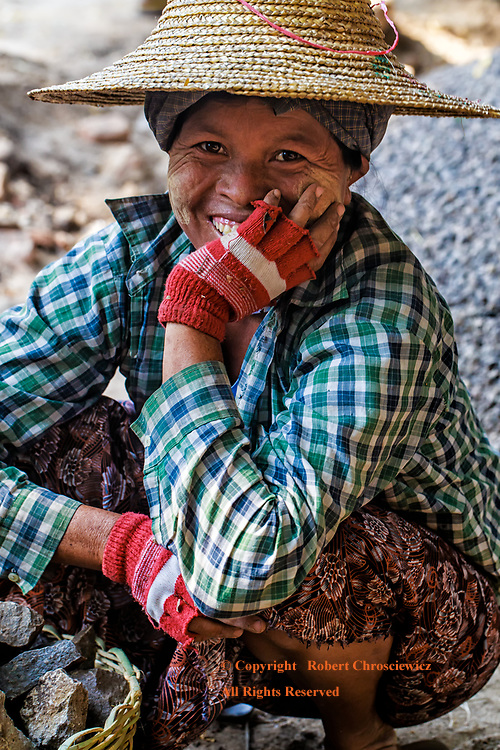 Road Crew Smile: A worker takes a moment from the chore of road construction, glancing up into the camera she can't help but smile at her new found celebrity, New Bagan Myanmar.